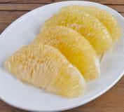 Куски свежего грейпфрута на белой плите Стоковое фото RF