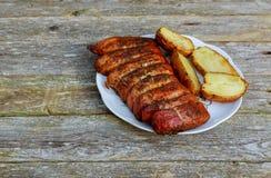 Куски стейка свинины барбекю на белой плите Зажаренные картошки на деревянной таблице Стоковое Изображение RF