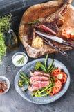 Куски стейка с томатами, спаржей и травами и на platt стоковые изображения