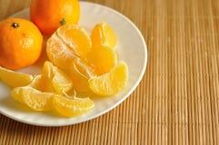 Куски сырцовых tangerines на белой плите Стоковое фото RF