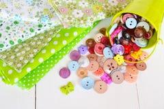 Куски ткани в точечных растрах цветка и польки Меньшее зеленое ведерко с декоративными красочными кнопками Стоковое Изображение