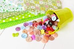 Куски ткани с картиной, разные кнопки, зеленое ведро Стоковая Фотография