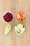 Куски томата и авокадоа с семенами гранатового дерева в шарах на таблице Стоковое Изображение