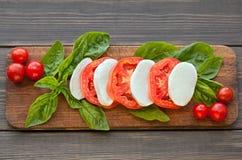 Куски томата и моццареллы с листьями базилика Стоковые Фото