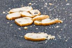 Куски хлеба лежат на дороге, концепции голода, позаботятся об еда, избалованный хлеб стоковое фото rf