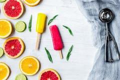 Куски цитруса с popsicles плодоовощ на взгляд сверху предпосылки таблицы Стоковые Изображения