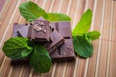 Куски шоколада с мятой на деревянной предпосылке Стоковые Фотографии RF