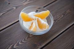 Куски югурта и апельсина в стеклянном блюде на деревянном столе Стоковые Изображения