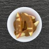 Куски Яблока покрытые с арахисовым маслом на таблице Стоковое Изображение RF