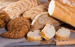 Куски wheaten хлеба и ножа на деревянной поверхности Стоковые Фото