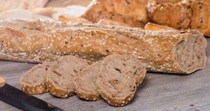 Куски wheaten хлеба и ножа на деревянной поверхности Стоковая Фотография RF