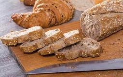 Куски wheaten хлеба и ножа на деревянной поверхности Стоковая Фотография