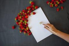 Кусок бумаги на черной предпосылке окруженной клубниками, женской руке с щеткой Стоковая Фотография RF