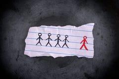 Кусок бумаги с вычерченными людьми и красным одним нечетное одно стоковые изображения rf