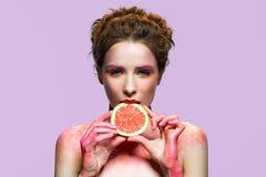 Кусок грейпфрута красивой девушки сдерживая Стоковое Изображение