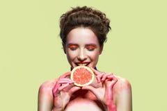 Кусок грейпфрута милой девушки сдерживая Стоковое Изображение