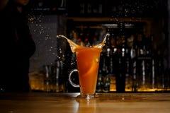 Кусок грейпфрута упал с брызгом в коктеиль спирта Стоковая Фотография