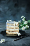 Кусок именниного пирога с цветки над голубой предпосылкой Стоковая Фотография