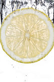 Кусок лимона падая в воду Стоковые Изображения
