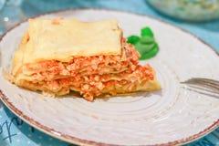Кусок лазаньи bolognese на белизне сделал по образцу плиту с базиликом и вилку на таблице стоковые фото
