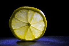 Кусок лимона на черной предпосылке в заднем свете стоковые фотографии rf