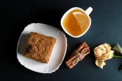 Кусок наслоенного торта меда Medovik украшенный с звездой анисовки на белой плите, ручках циннамона, чашке чаю с лимоном, высушен Стоковая Фотография RF