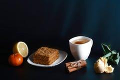 Кусок наслоенного торта меда Medovik украшенный с звездой анисовки на белой плите, ручках циннамона, чашке чаю с лимоном, tangeri Стоковые Изображения
