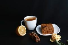 Кусок наслоенного торта меда Medovik украшенный с звездой анисовки на белой плите, ручках циннамона, чашке чаю с лимоном, местом  Стоковая Фотография