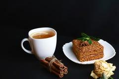 Кусок наслоенного торта меда Medovik украшенный с мятой на белой плите, ручках циннамона, чашке чаю при высушенный лимон, поднял, Стоковое Фото