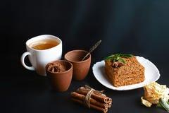 Кусок наслоенного торта меда Medovik украшенный с мятой на белой плите, ручках циннамона, чашке чаю с лимоном, местом для tex Стоковые Изображения