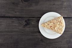Кусок наслоенного торта с гайкой на плите, на деревянном столе, задняя часть темноты Стоковое Изображение RF