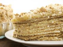 Кусок наслоенного торта с гайкой на плите, на деревянном столе, задняя часть темноты Стоковое Фото