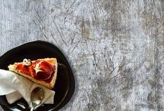 Кусок пирога и черная плита на старой деревянной unpainted поверхности Стоковое Фото