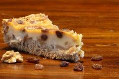 Кусок пирога на коричневых древесине, изюминках и грецких орехах Стоковая Фотография RF
