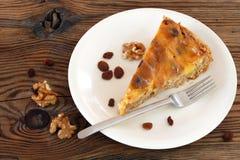 Кусок пирога, некоторые изюминки, грецкие орехи и торт развлетвляют на oldwood Стоковые Фото