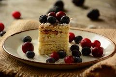 Кусок пирога napoleon на плите с сладостными свежими ягодами Стоковое Фото