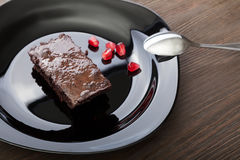 Кусок пирожного на черной плите на деревянном столе с ложкой a Стоковое Фото