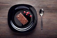 Кусок пирожного на черной плите на деревянном столе Стоковые Изображения RF