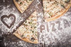 Кусок пиццы на деревянной предпосылке Стоковое Изображение