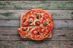 Кусок пиццы на деревянной прерывая доске Взгляд сверху Стоковое Изображение RF
