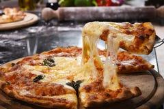 Кусок пиццы поднимаясь на деревянной доске Стоковые Изображения