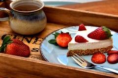 Кусок сырцового белого торта клубники на голубой плите с чашкой кофе здоровая принципиальная схема завтрака стоковые фотографии rf