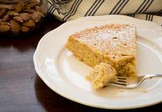Кусок торта миндалины лимона с вилкой на белой плите Стоковое Изображение RF