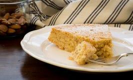 Кусок торта миндалины лимона с вилкой на белой плите Стоковое Изображение