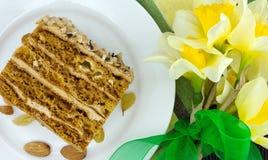 Кусок торта с гайкой на плите Букет желтого daffodil Стоковая Фотография