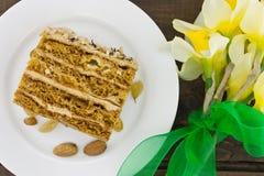 Кусок торта с гайкой на плите Букет желтого daffodil Стоковое Фото