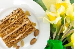 Кусок торта с гайкой на плите Букет желтого daffodil Стоковые Фото