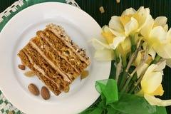 Кусок торта с гайкой на плите Букет желтого daffodil Стоковые Изображения RF