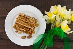 Кусок торта с гайкой на плите Букет желтого daffodil Стоковое Изображение RF