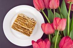 Кусок торта с гайкой на плите Букет тюльпанов Взгляд сверху Стоковое Фото
